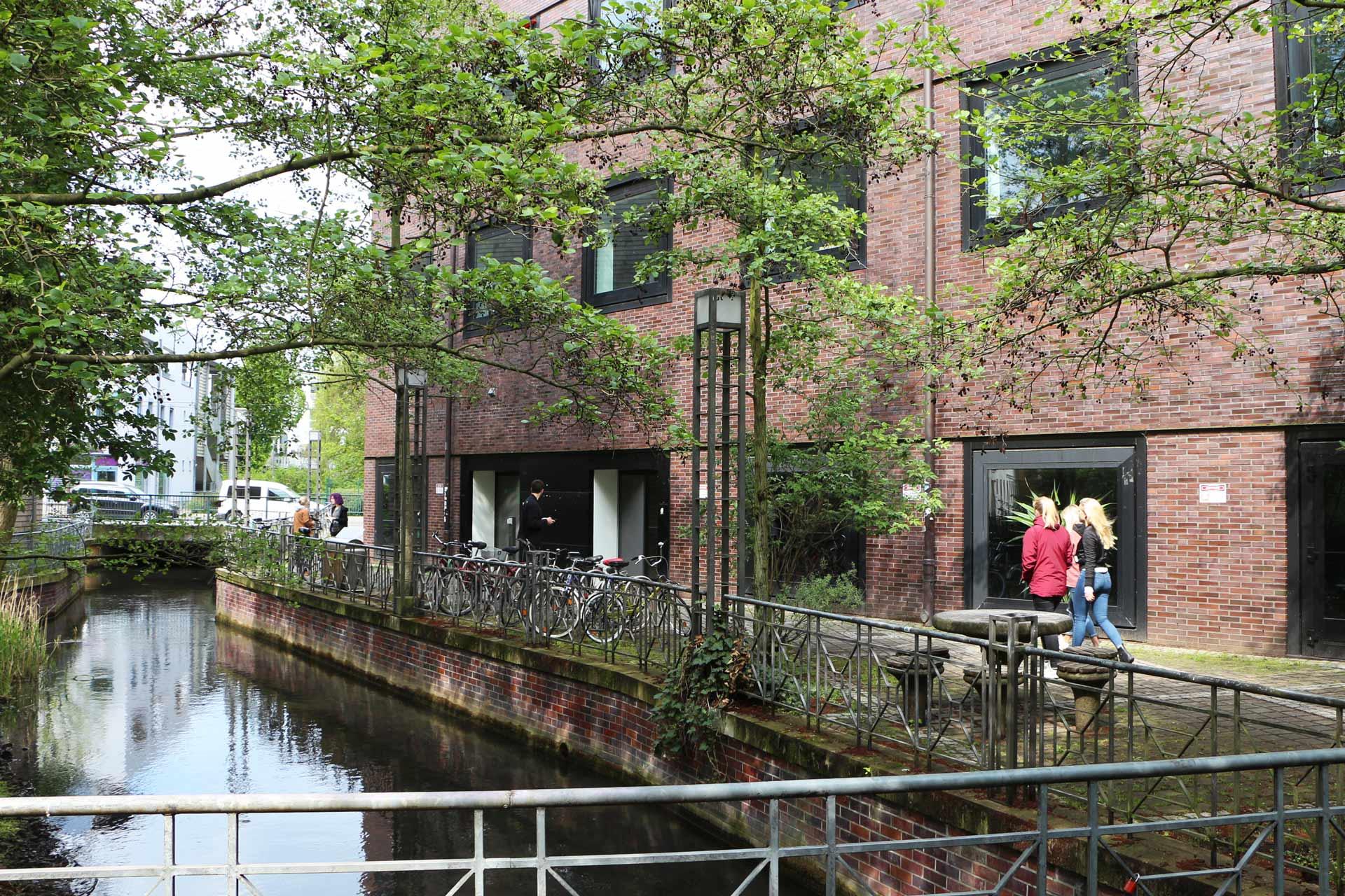 Ein Fluss fließt neben einem Gebäude auf dem Campus.