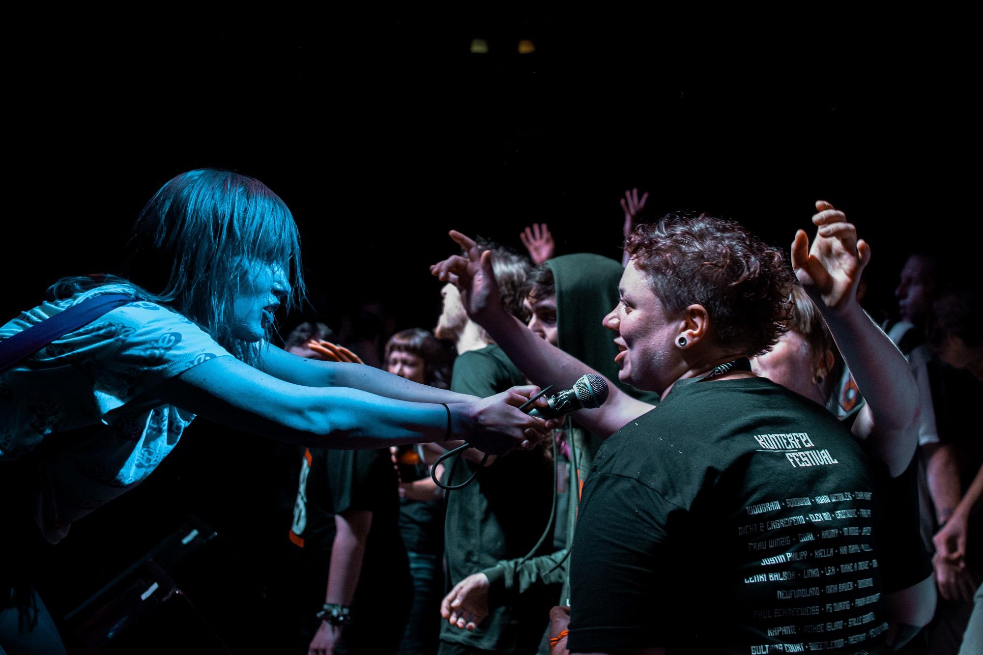 Sängerin hält einer Zuschauerin das Mikro entgegen