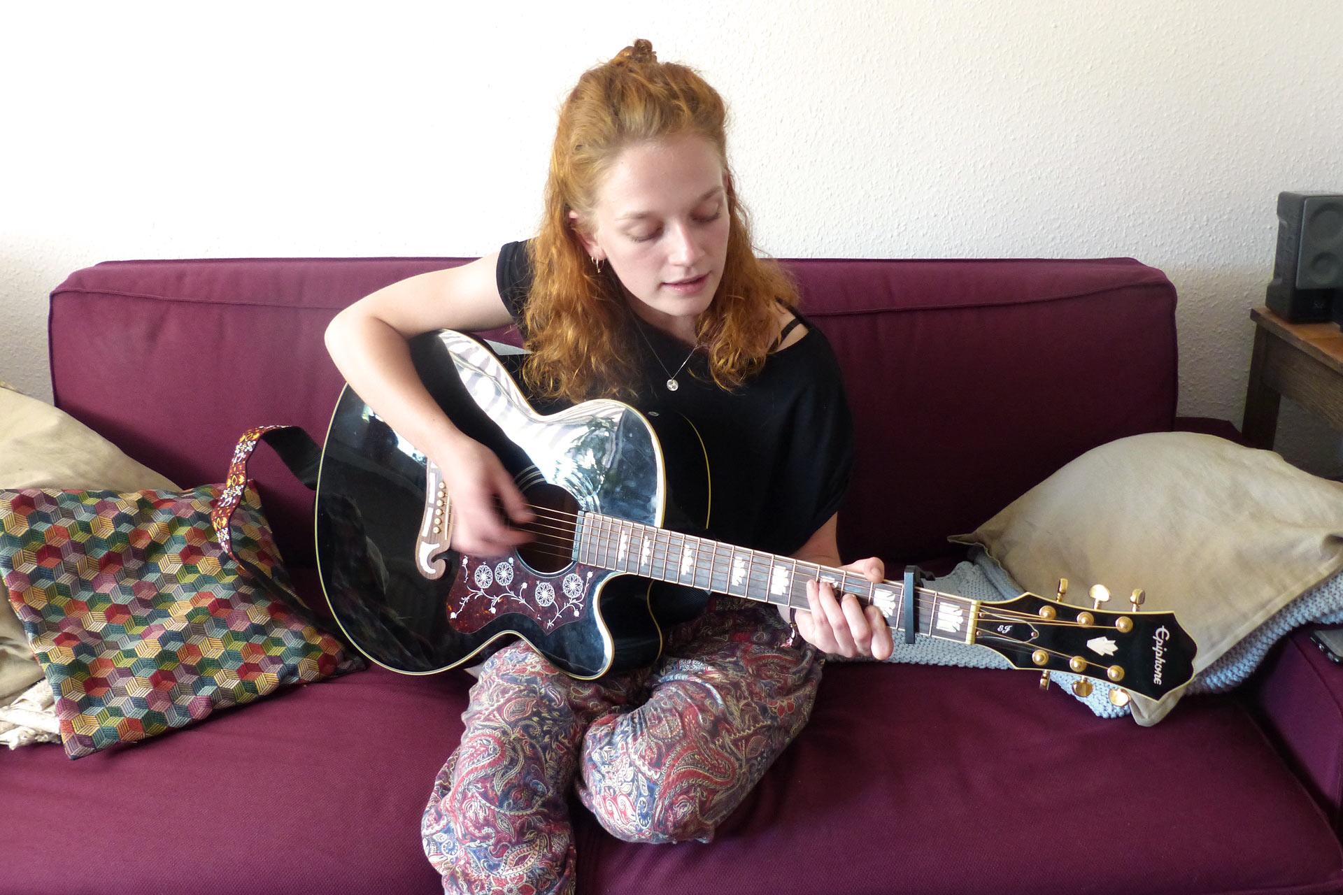 Nina spielt auf ihrer Gitarre.