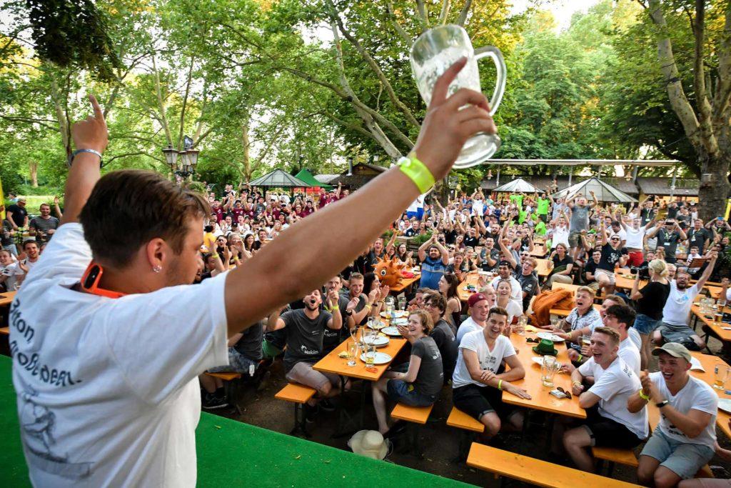 Feiernde Student mit leeren Bierglas in der Hand vor einen vollem Biergarten
