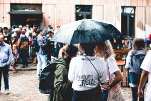 Helferinnen unter einem Regenschirm vor dem Casino