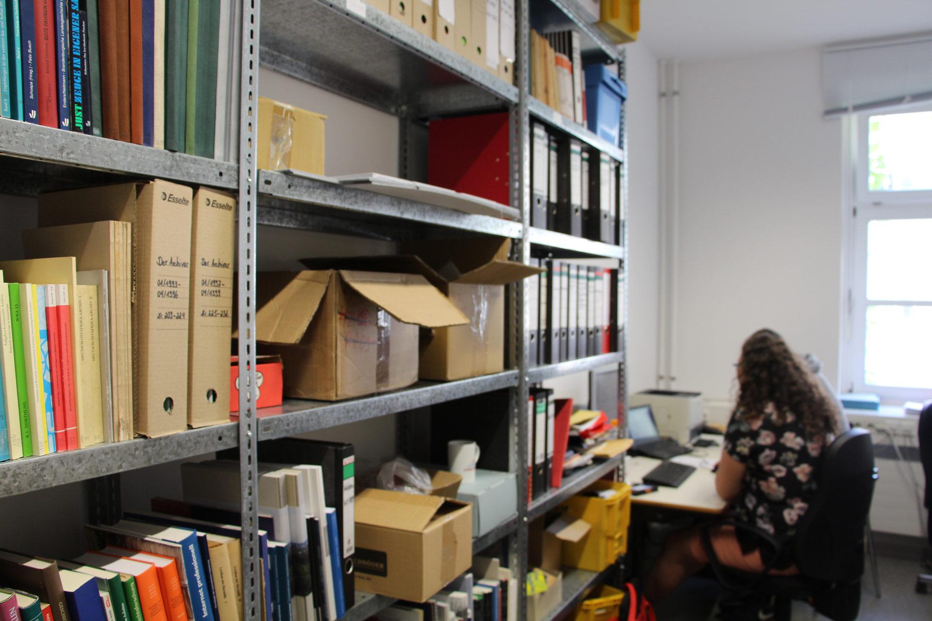 Büro des Hochschularchives mit vollgestellten Regalen