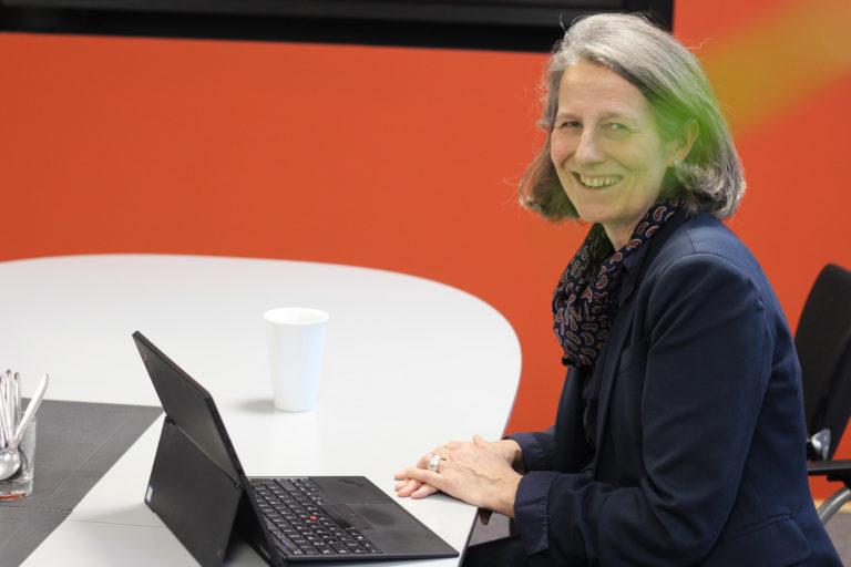 Eva Schmitt-Rodermund sitzt an ihrem Tisch und lächelt in die Kamera