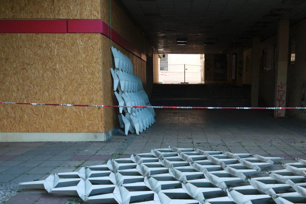 Abmontierte Sternenelemente liegen auf dem Boden, andere sind an der Wand angelehnt im abgeschlossenen Außenbereich des ehemaligen FH-Gebäudes.
