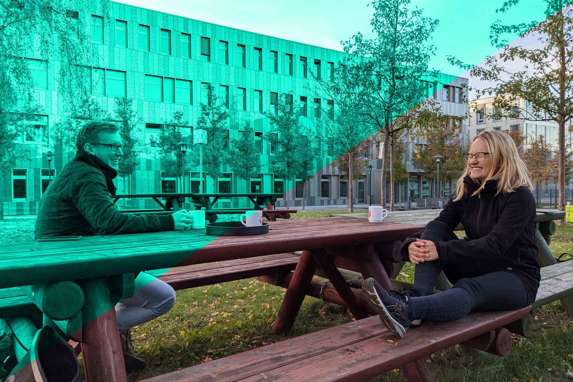 Christian und Sophia sitzen auf einer Bank auf der Campuswiese der FH Potsdam