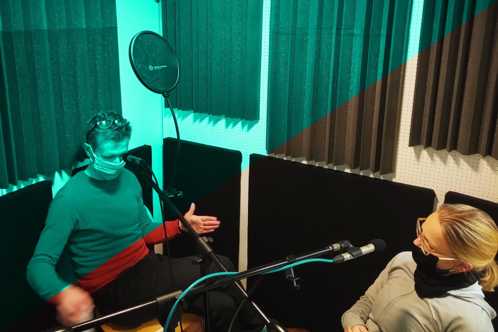 Christian und Sophia sitzen mit Mund-Nasen-Schutz im Aufnahmelabor