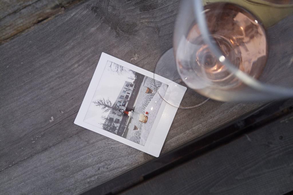 Polaroid mit Sektgläsern und Flasche vor dem Hauptgebäude der FHP, darauf steht zum Teil ein halbvolles Sektglas