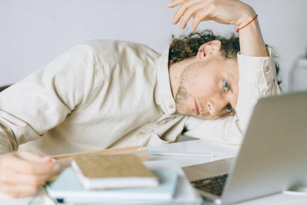Person sitzt, lehnt dabei den Kopf auf einen Arm und schaut auf einen Laptop