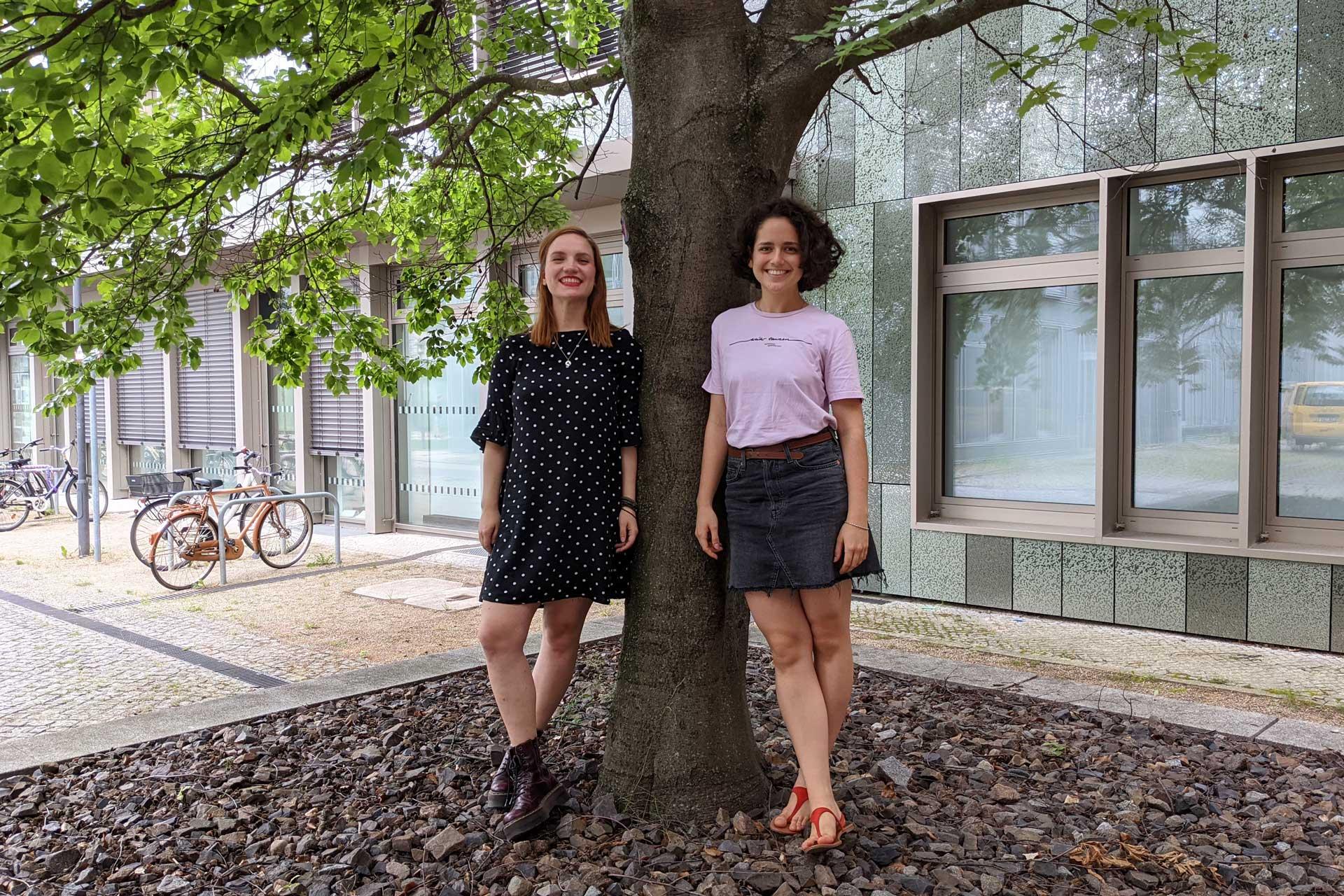 Elisa und Melissa lehnen sich an einen Baum.