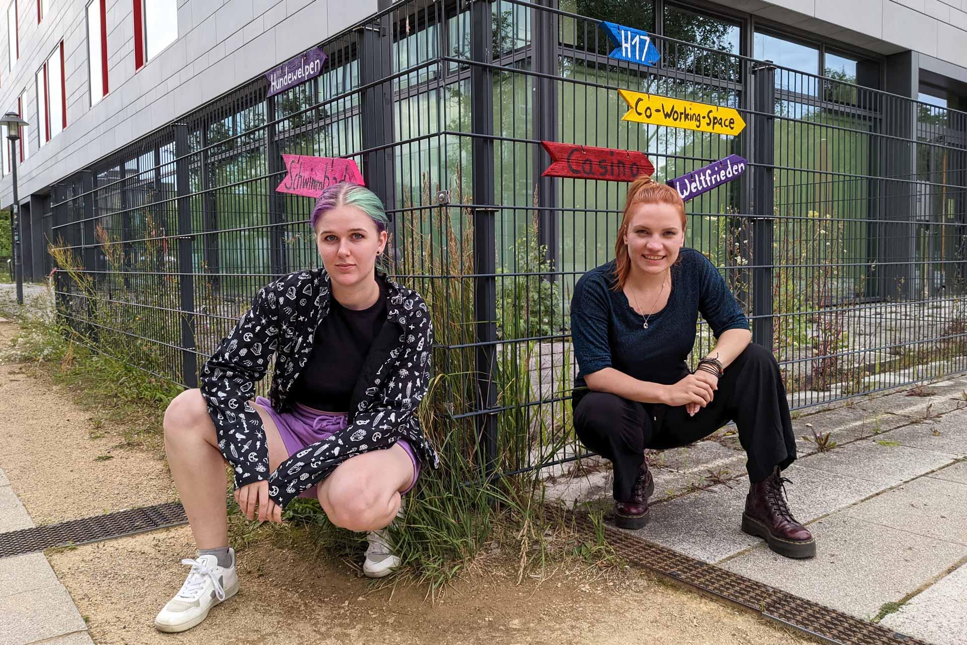 Elena und Elisa stehen draußen vor einem Gitter, an dem bunte Schilder angebracht sind.