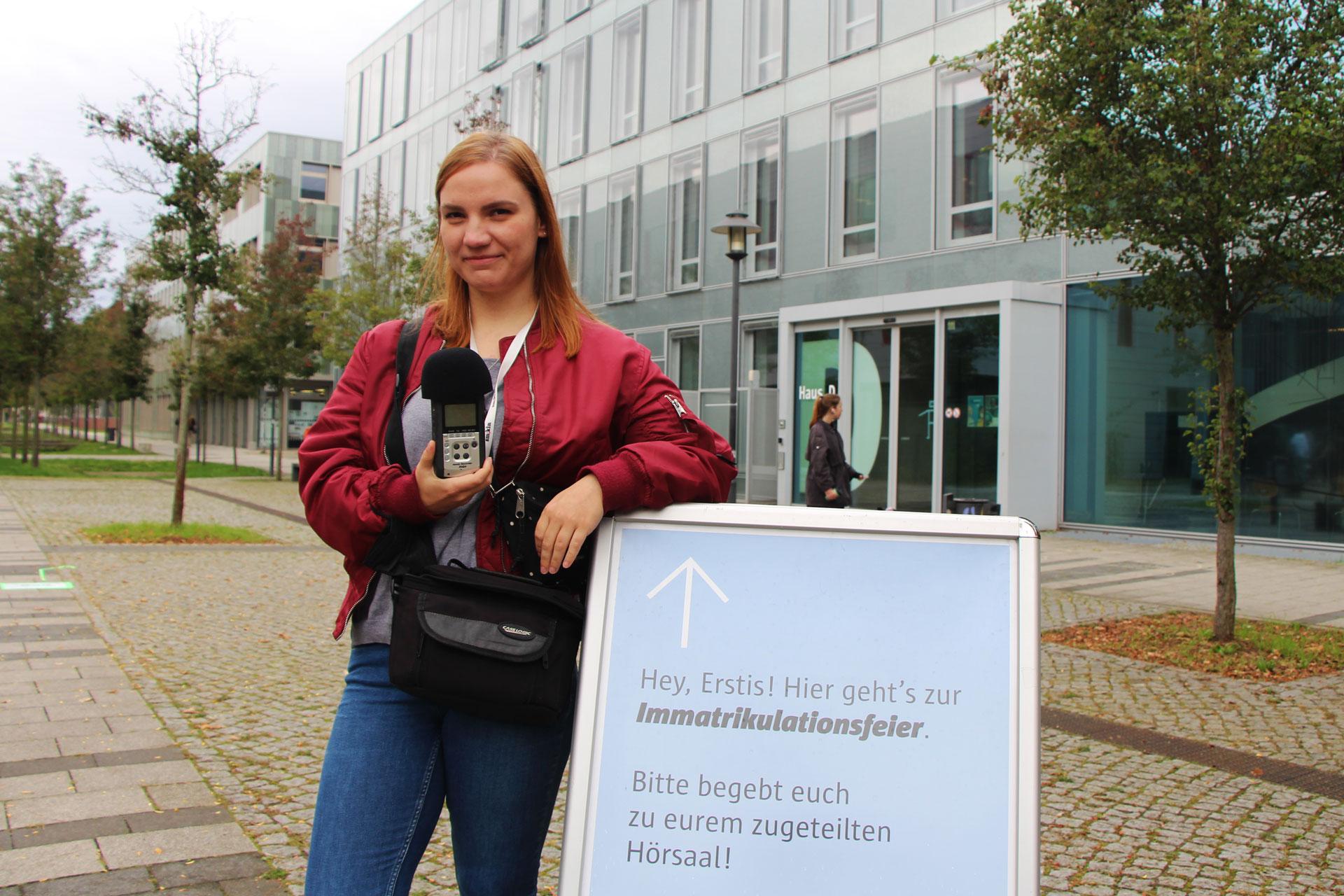 Elisa steht mit ihrem Aufnahmegerät draußen auf dem Campus.